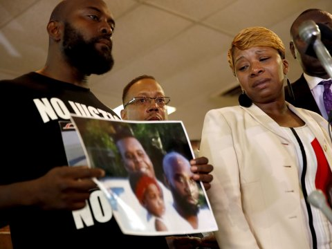 Lesley McSpadden, right, the mother of 18-year-old Michael Brown, watches as Brown's father, Michael Brown Sr., holds up a family picture. AP Images