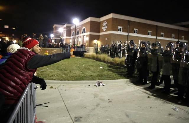 Protesters confront law enforcers in Ferguson following the jury's verdict. Photo by David Goldman/AP