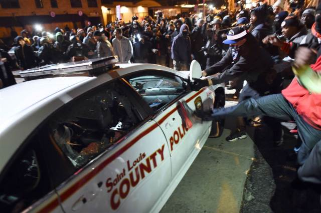 Demonstrators vandalizing and attacking police vehicles in Ferguson following the decision.  Photo by Jewel Samad/AFP